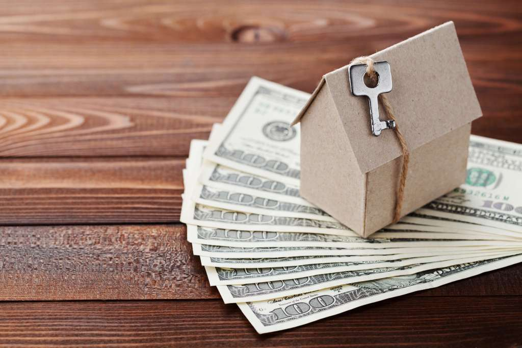 Model of cardboard home with key and dollar money. House building, insurance, housewarming, loan, real estate, cost of housing or buying a new home concept.